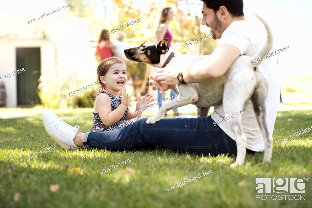 Stock Photo: Happy father, daughter and dog in garden.