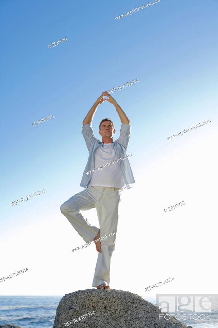 Stock Photo: Man standing on one leg, doing yoga on top of rock with ocean in background.