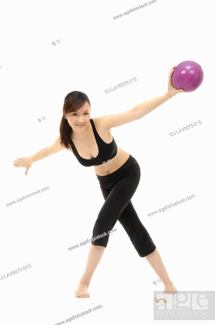 Stock Photo: Young woman doing stretching exercise with fitness ball.