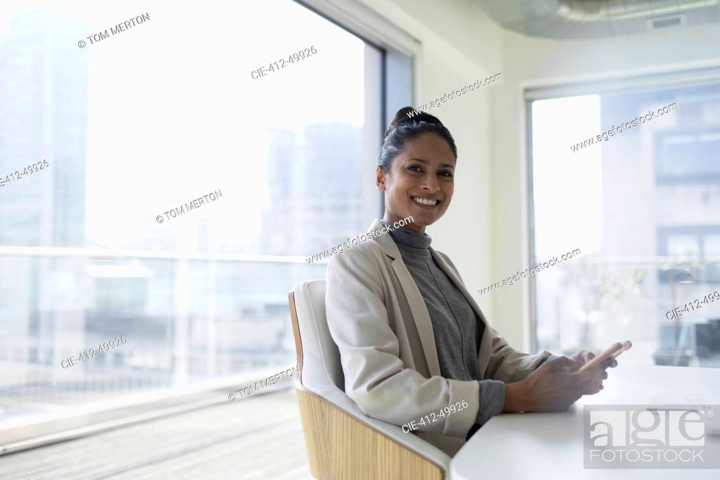 Stock Photo: Portrait happy, confident businesswoman with smart phone in conference room.