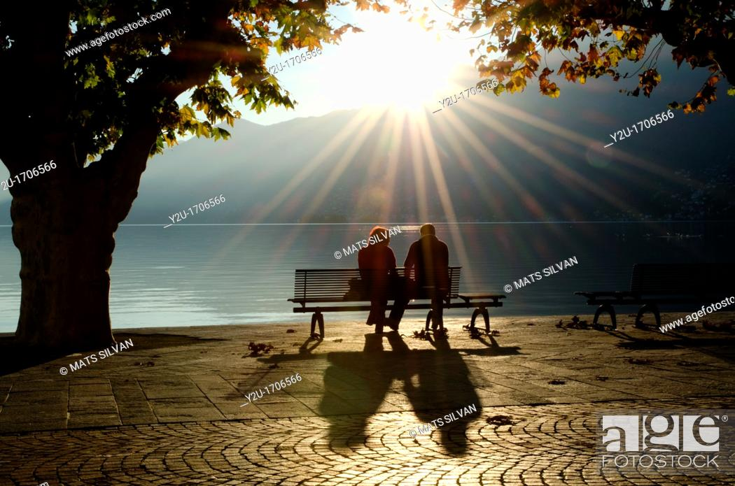 Stock Photo: Couple on a bench between two trees on the lake front with shadows and sunbeam.