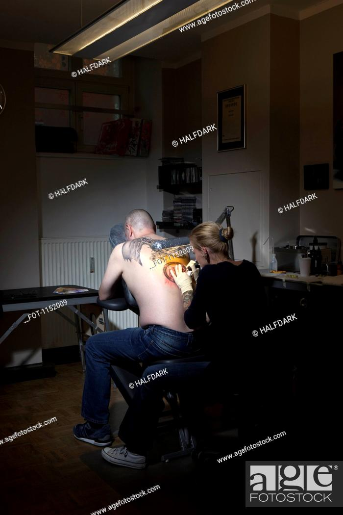 Stock Photo: A female tattoo artist tattooing a man's back in a tattoo shop.