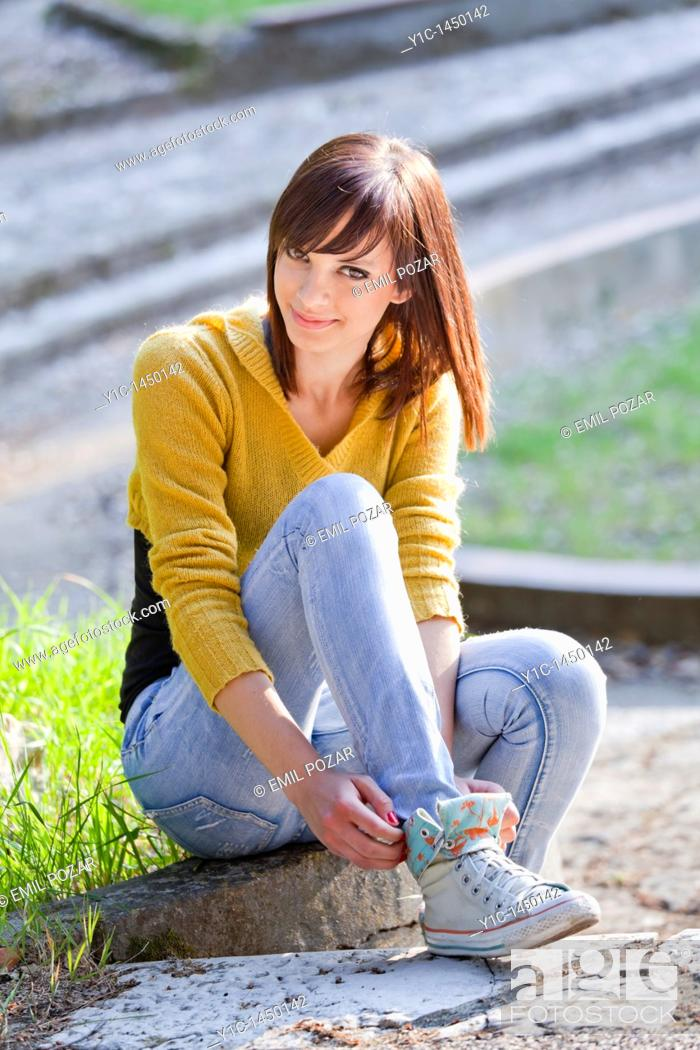 Stock Photo: Attractive young woman is adjusting her sneakers in the park, smiling.