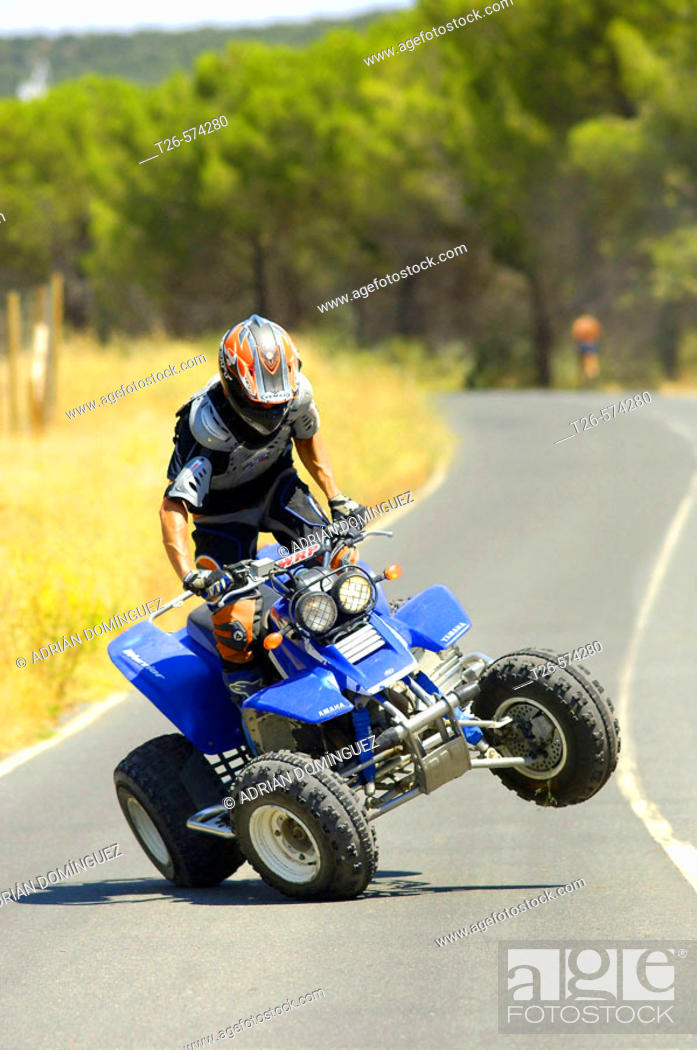 Stock Photo: Man driving a quad on a lonely road.