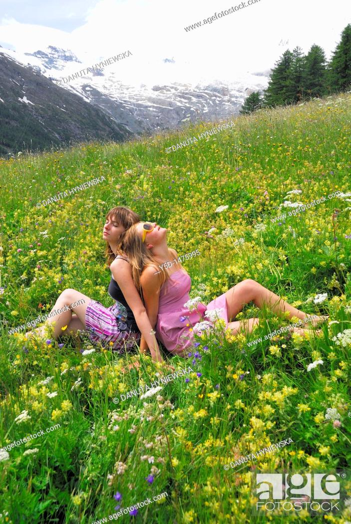 Stock Photo: Two young women sitting, arm in arm, in flowers, mountains, Saas Fee, Swiss Alps, Switzerland.