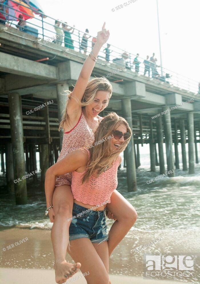 Stock Photo: Two young women playing piggy backs near pier, Santa Monica, California, USA.