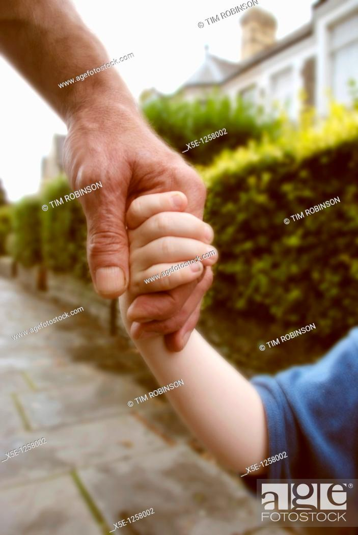 Stock Photo: Adult male hand holding hand of 3 year boy in suburban street.