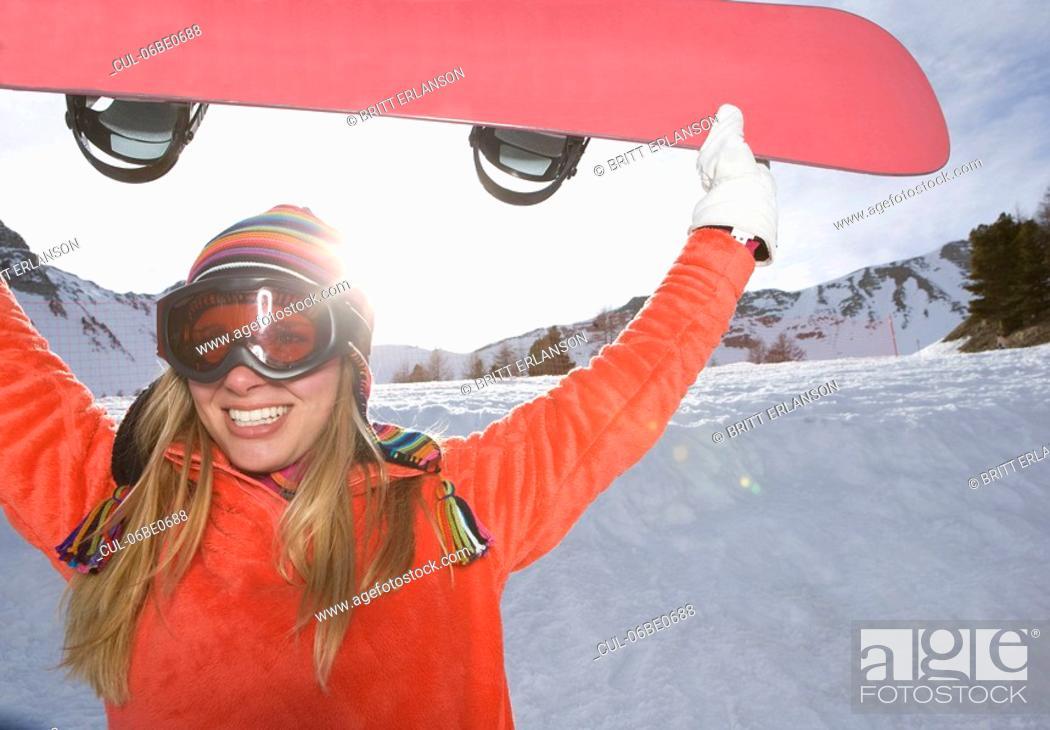 Stock Photo: Girl lifting ski board, smiling.