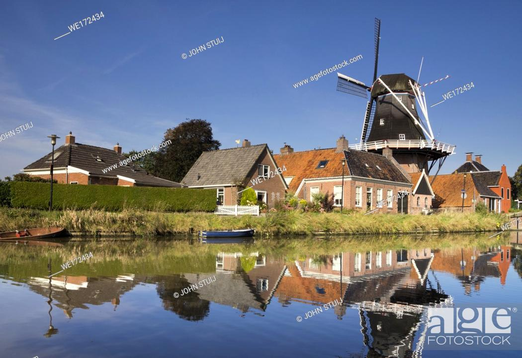 Stock Photo: The Hunsingo windmill along the Boterdiep canal in the Dutch village Onderdendam.