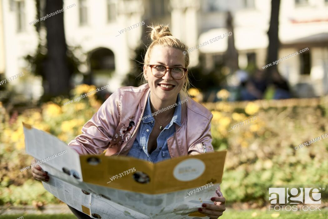 Stock Photo: Woman with city guide map in park, in Berlin, Germany,.