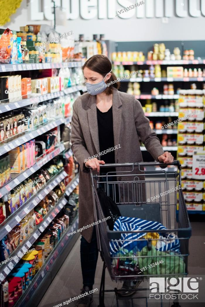 Stock Photo: Woman with mask in supermarket.