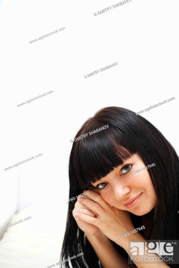 Stock Photo: pretty brunette girl indoors on the bed smiling.