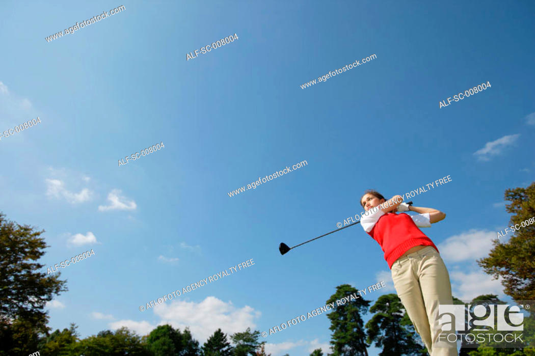 Stock Photo: Young woman playing golf.