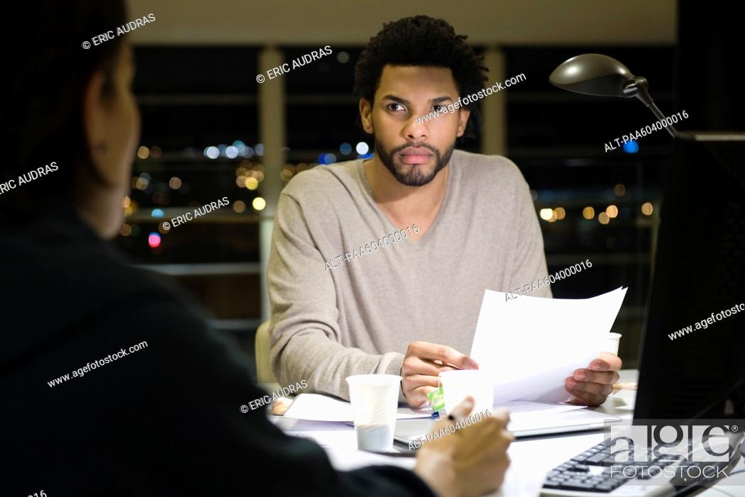 Stock Photo: Colleagues working on project together in office at night.