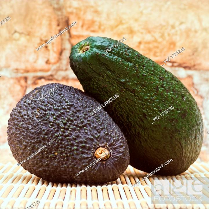 Stock Photo: Two avocados on bamboo mat.