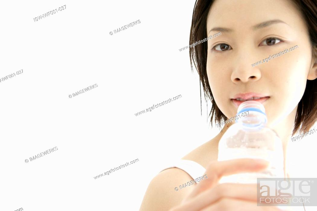 Stock Photo: Front view of a young woman drinking water after her exercise.