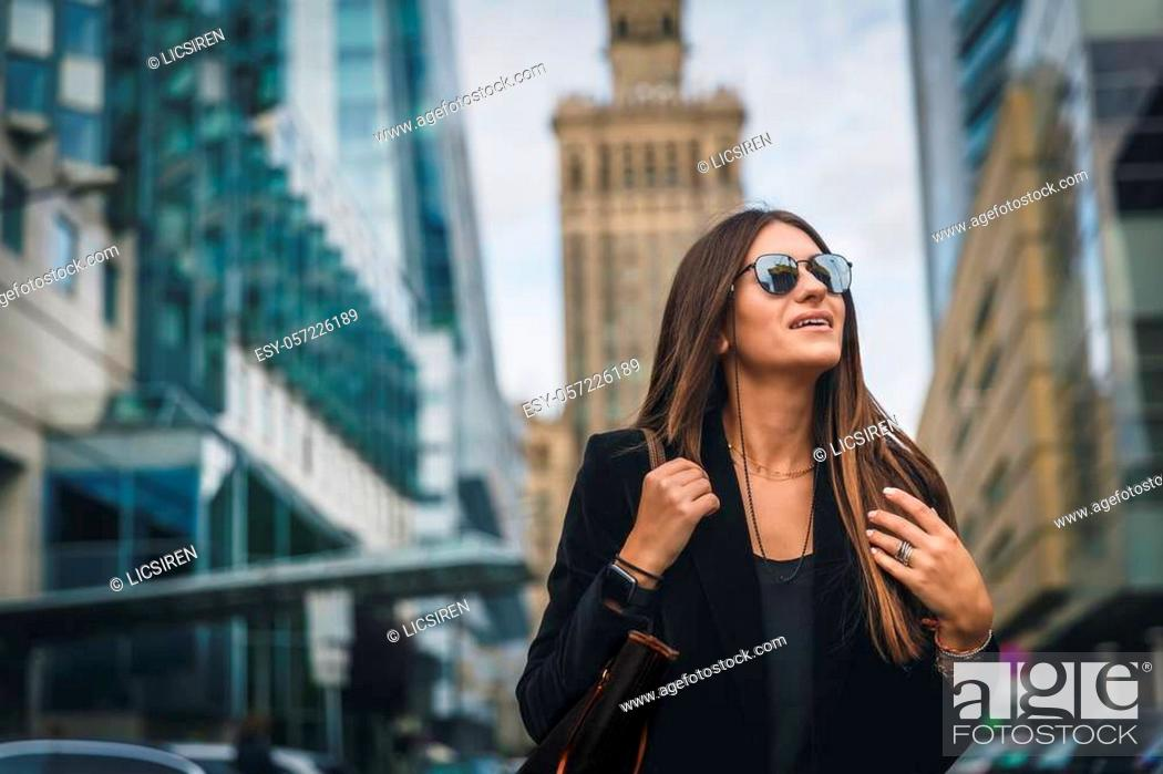 Stock Photo: Close-up Fashion woman portrait of young pretty trendy girl posing at the city in Europe. Beautiful stylish woman in Sunglasses walking on street.