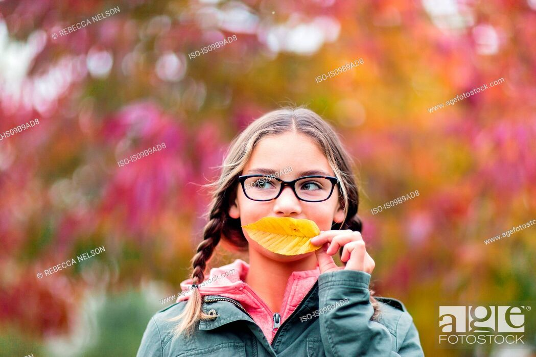 Stock Photo: Portrait of girl with plaits and glasses covering mouth with leaf looking away.