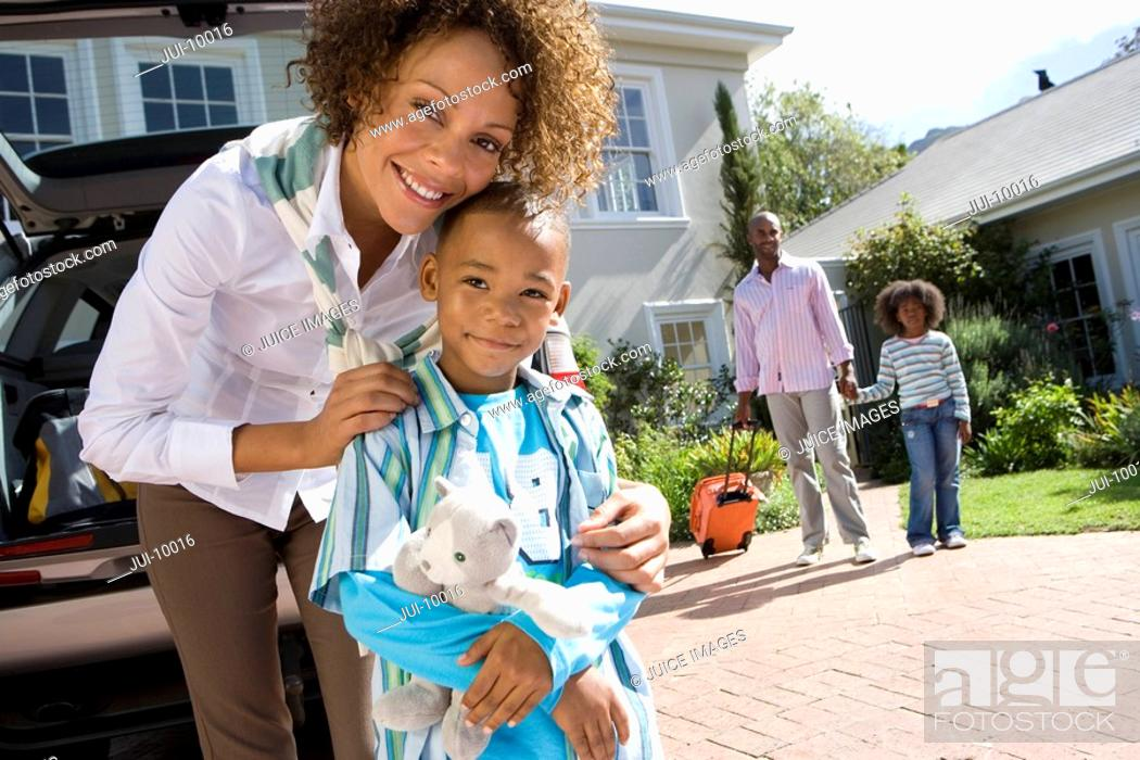 Stock Photo: Mother embracing son 6-8 in driveway, father and daughter 8-10 in background, smiling, portrait.