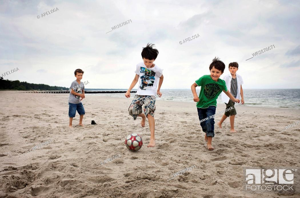 Photo de stock: Brothers playing soccer on sand at beach against sky.