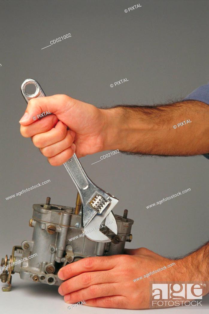Stock Photo: Monkey wrench and carburetor.