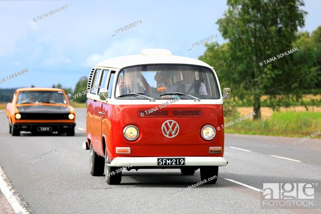 Stock Photo: Classic Volkswagen red and white Type 2 camper van moves along highway on Maisemaruise 2017 car cruise summer event in Tawastia Proper, Finland.
