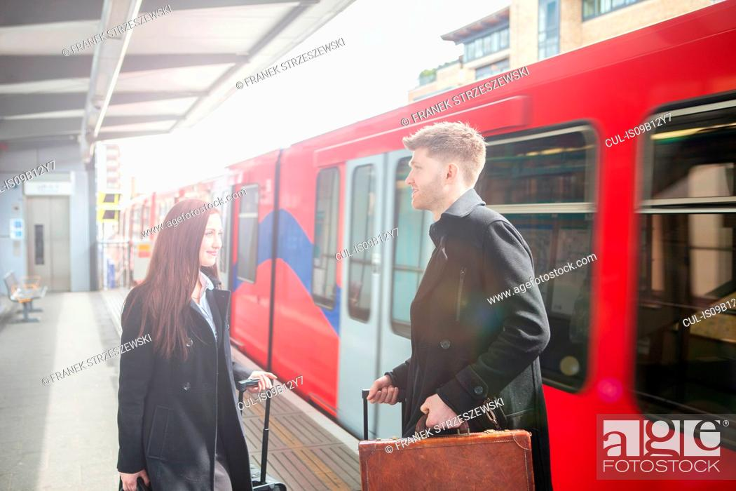 Imagen: Businesswoman and businessman in Docklands Light Railway train station, London.