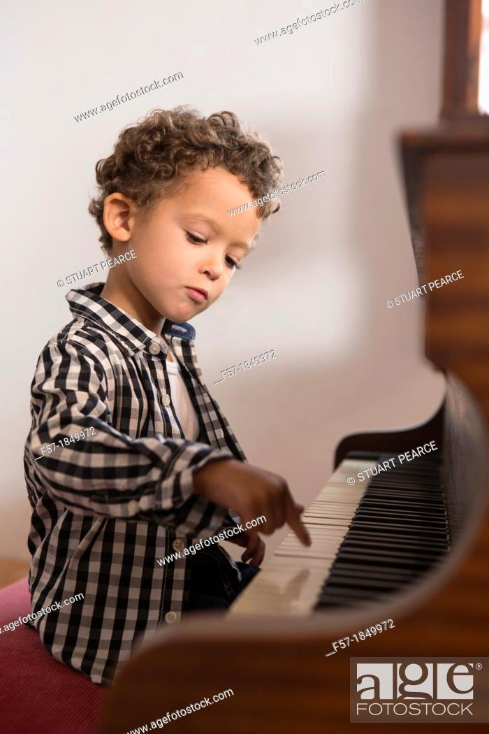 Stock Photo: Four year old boy playing the piano.