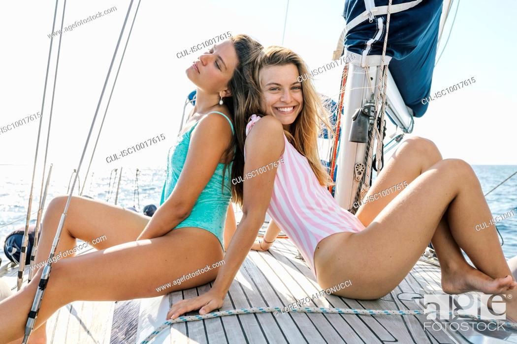 Imagen: Friends sunbathing on deck of sailboat, Italy.