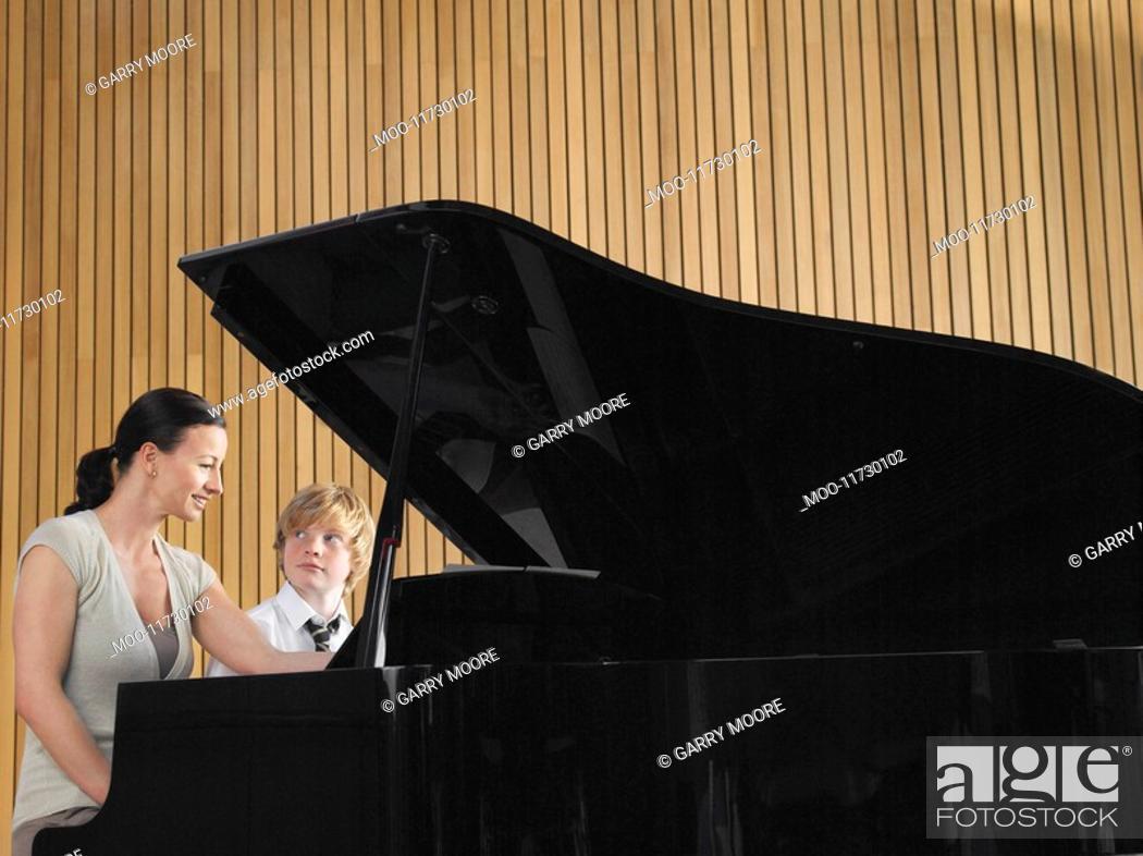 Stock Photo: Teacher with student sitting at piano in music class.