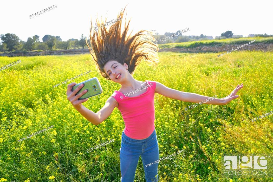 Imagen: Teen girl selfie video photo in spring meadow moving hair.
