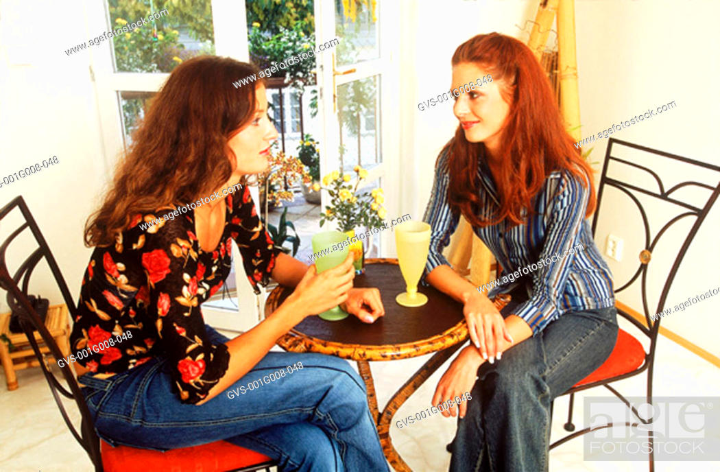 Stock Photo: Two young woman sitting together having a drink.