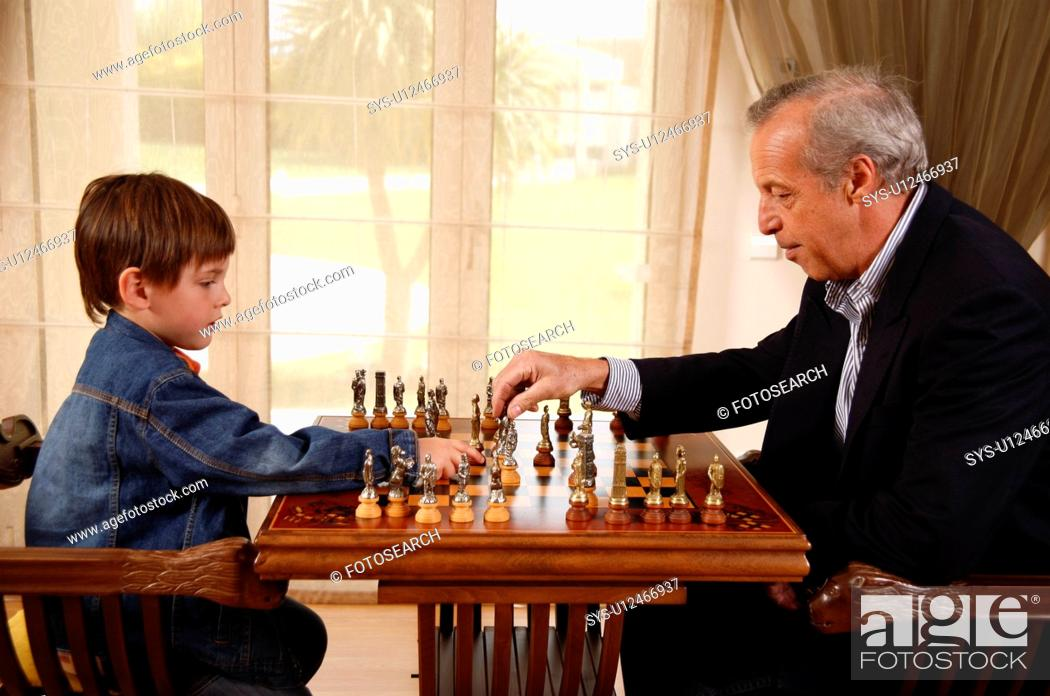 Stock Photo: Mature man and little boy playing chess.
