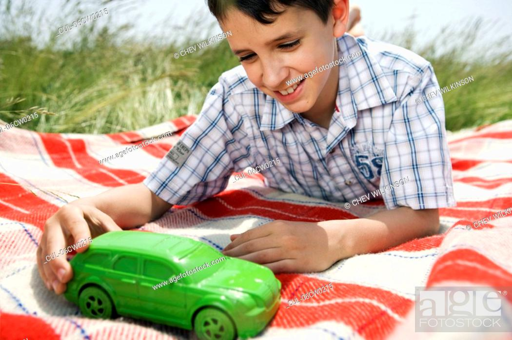 Stock Photo: Boy playing with green toy car.