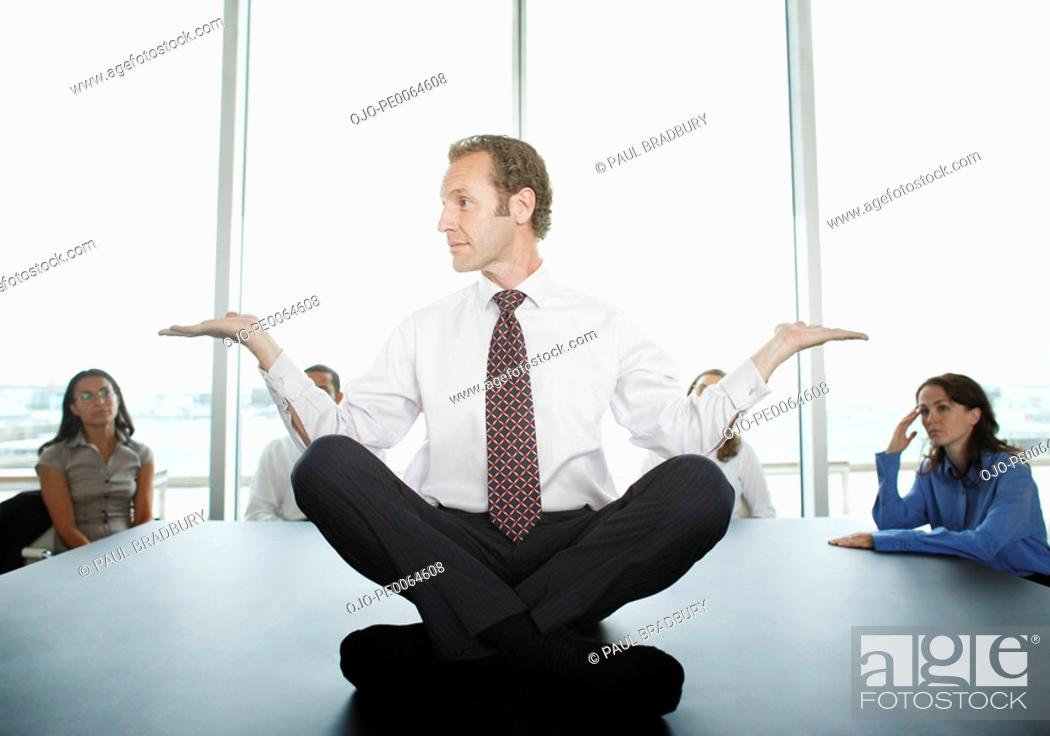 Stock Photo: Businessman doing yoga in conference room.