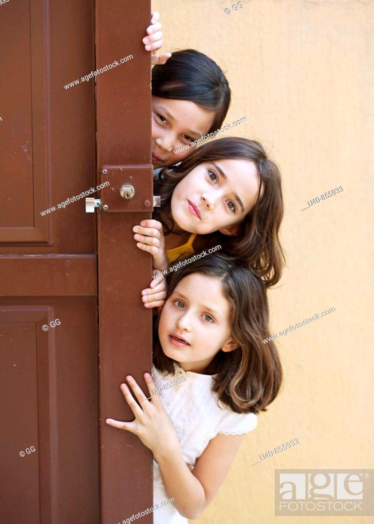 Stock Photo: Girls peeking from behind door.
