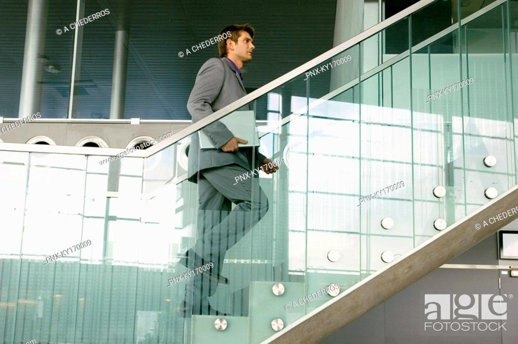 Stock Photo: Businessman carrying a laptop and moving up a staircase.