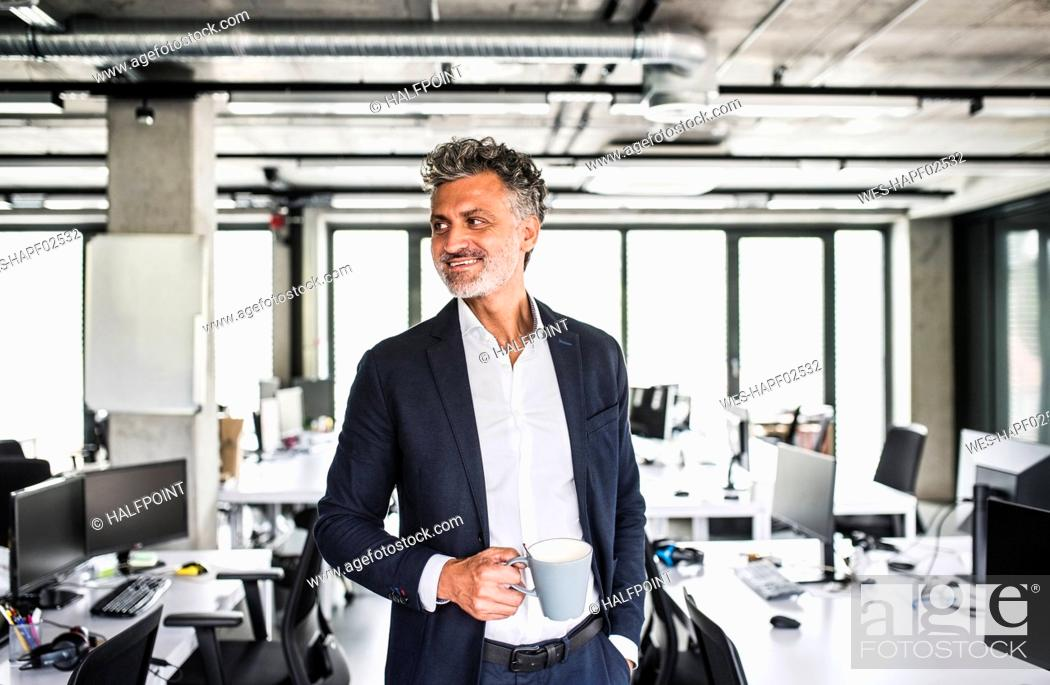 Stock Photo: Smiling mature businessman with coffee mug in office.