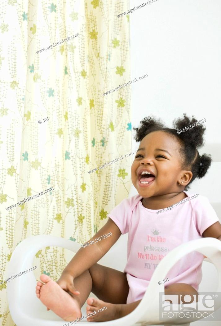 Stock Photo: African American girl laughing in chair.