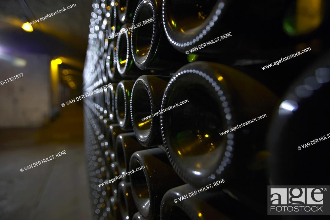 Stock Photo: A close-up of bottle bottoms in an aisle of a wine cellar.
