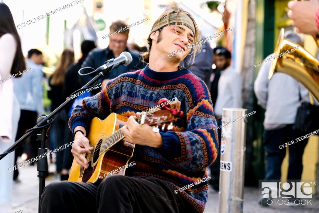 Imagen: Young man playing guitar in the street.