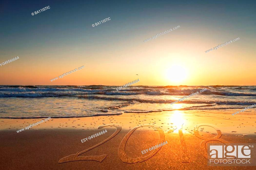 Stock Photo: 2018 written on the sand of a beach, travel 2018 new year concept.