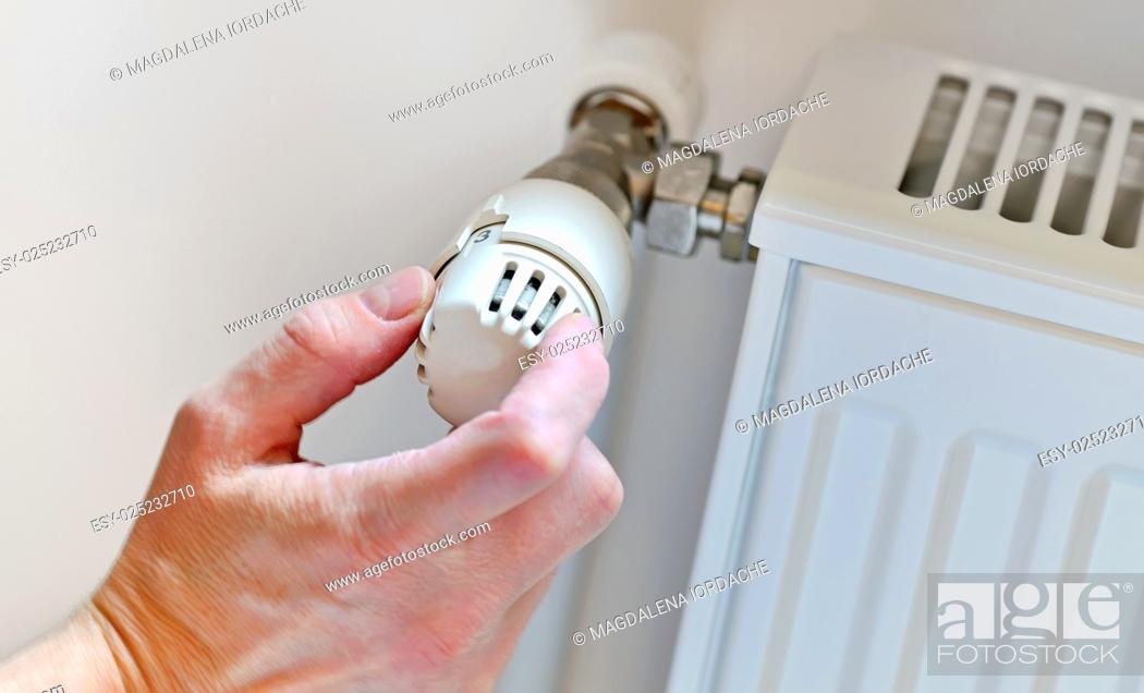 Stock Photo: Hand Adjusting Heater Thermostat in winter time.