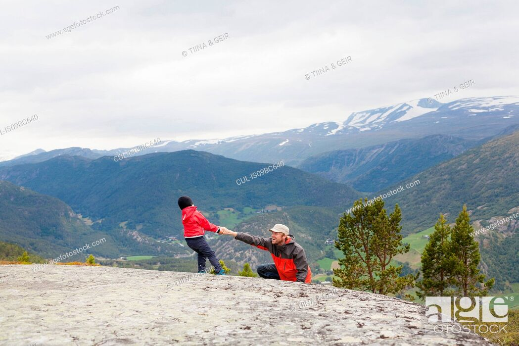 Stock Photo: Boy helping hiker father over rock in mountain landscape, Jotunheimen National Park, Lom, Oppland, Norway.