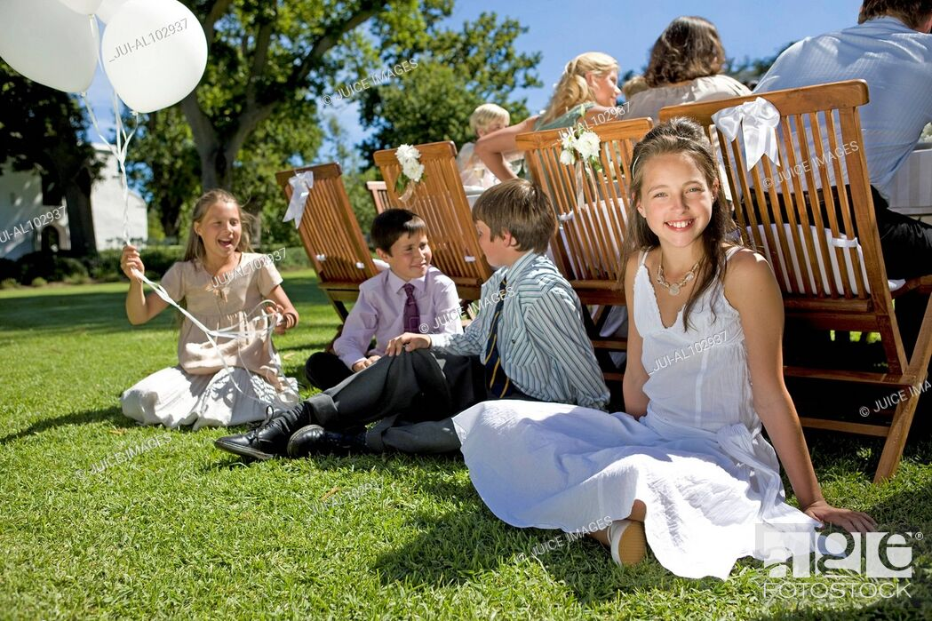 Stock Photo: A group of young children sitting on the grass at a wedding reception.