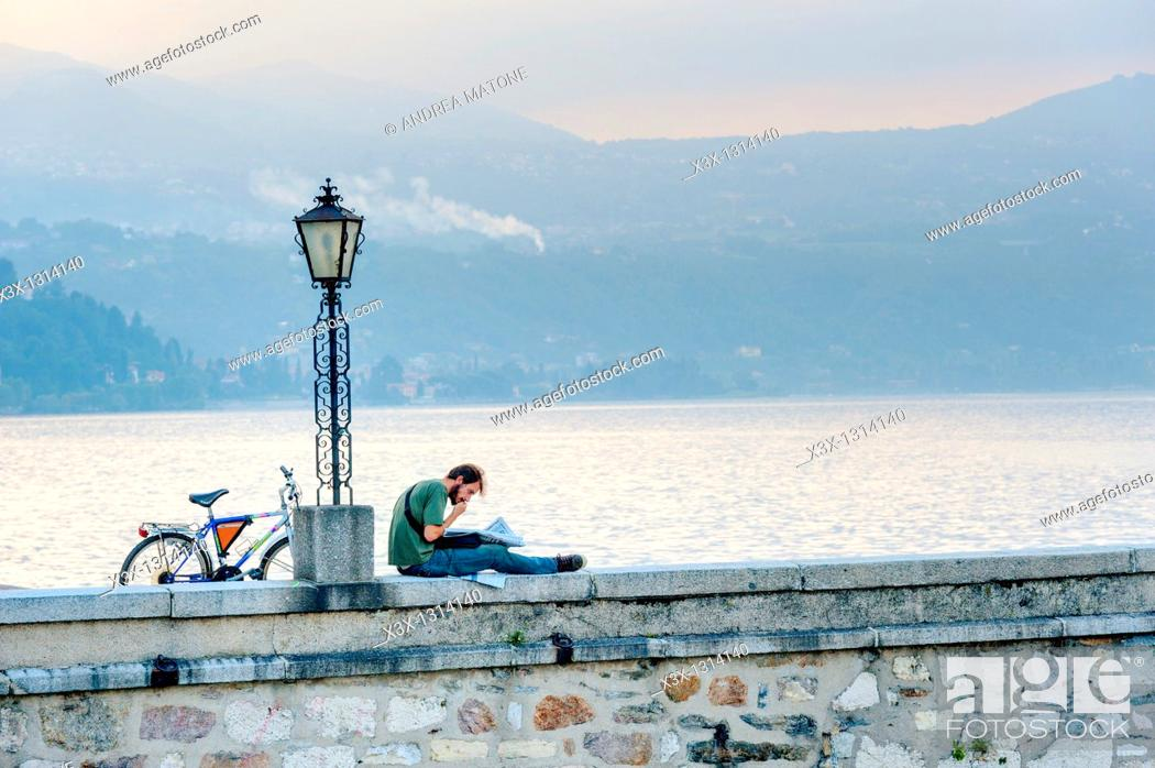 Stock Photo: Man reading a newspaper in the town of Arona Lago Maggiore Italy.