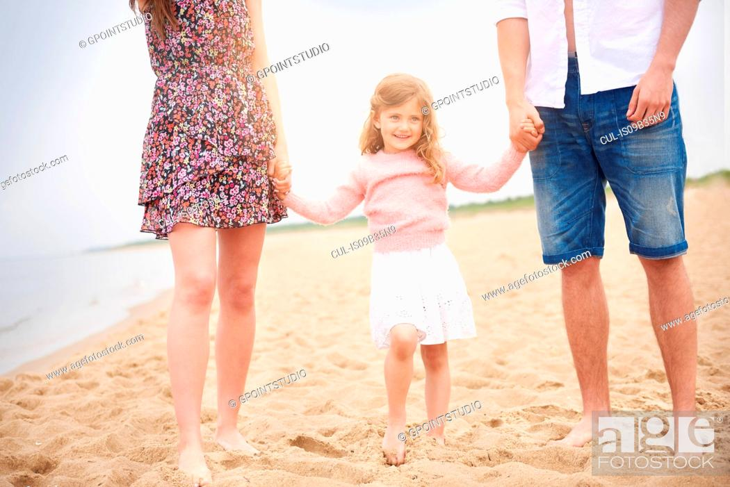Stock Photo: Family holding hands walking on beach.