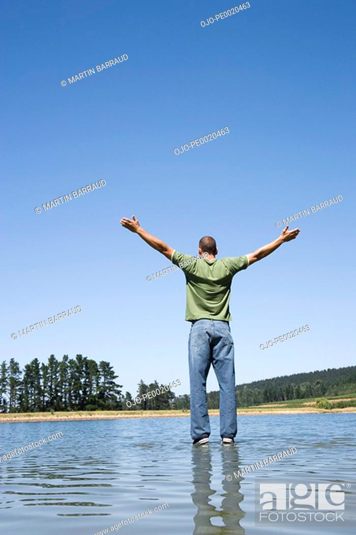 Stock Photo: Man standing on water with arms up.