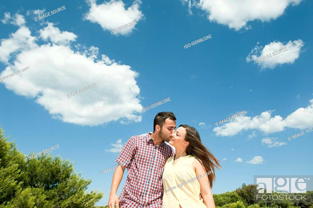 Stock Photo: Affectionate young man kissing girlfriend.