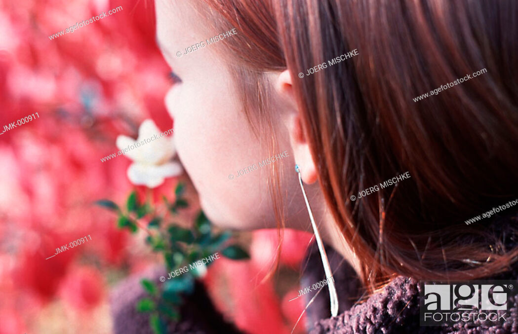 Stock Photo: Portrait of a little girl in the garden, taking a smell at a flower.
